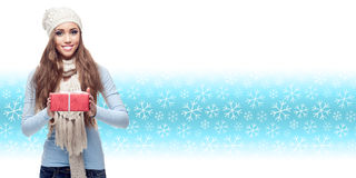 Happy young woman holding gift over winter background Stock Photo