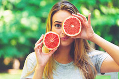Happy Young Woman Holding Grapefruit Stock Image