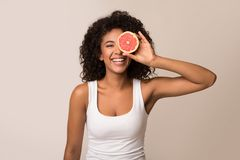 Happy young woman holding half of grapefruit. Happy young black woman holding half of grapefruit on light background royalty free stock images