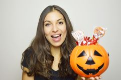 Happy young woman holding Halloween bucket Jack o lantern full of sweets. Isolated gray background. Royalty Free Stock Photo