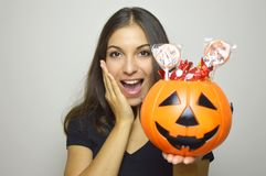 Happy young woman holding Halloween bucket Jack o lantern full of sweets. Isolated gray background. Royalty Free Stock Photos