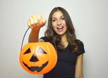 Happy young woman holding Halloween bucket Jack o lantern. Isolated gray background. Royalty Free Stock Photography