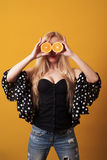 Happy young woman holding halvesof oranges over yellow background. stock images