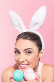 Happy young woman holding a handful of Easter eggs Royalty Free Stock Images