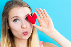 Happy young woman holding a heart cushion Stock Photo