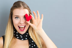 Happy young woman holding a heart cushion. On a gray background royalty free stock photos