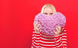 Happy young woman holding a heart cushion. On a red background royalty free stock photo