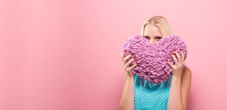 Happy young woman holding a heart cushion. On a solid background stock photos