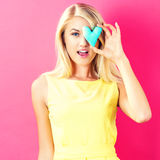 Happy young woman holding a heart cushion Stock Photography
