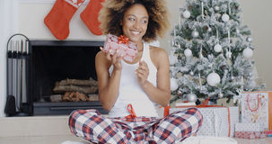 Happy young woman holding her Christmas gift Royalty Free Stock Photos