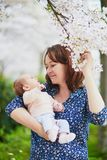 Happy young woman holding her little baby girl stock photos