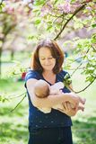 Happy young woman holding her little baby girl royalty free stock image