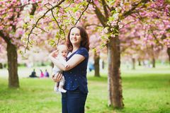 Happy young woman holding her little baby girl stock photo