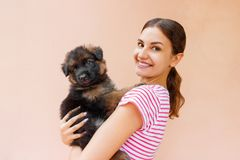 Happy young woman holding her pet puppy on orange background.  stock photos