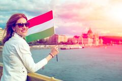 Happy young woman holding Hungarian flag at Budapest in sunset. Hungary stock photography
