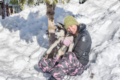 Happy young woman holding husky puppy in the snow Royalty Free Stock Photo