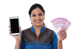 Happy young woman holding Indian currency and cellphone Royalty Free Stock Photography