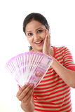 Happy young woman holding Indian 2000 rupee notes. Against white royalty free stock photography