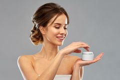 Happy young woman holding jar of cream stock images