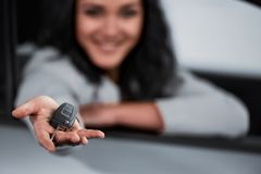 Car sales. Happy young woman is holding keys to new car and looking at the camera. Focus on keys stock photography