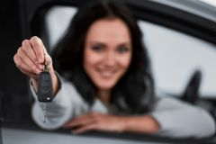 Car sales. Happy young woman is holding keys to new car and looking at the camera. Focus on keys stock images