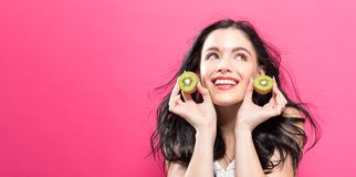 Happy young woman holding kiwis. On a pink background stock image