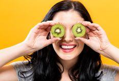 Happy young woman holding kiwis. On a yellow background stock photography