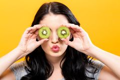 Happy young woman holding kiwis. On a yellow background royalty free stock image