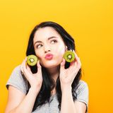 Happy young woman holding kiwis. On a yellow background stock images