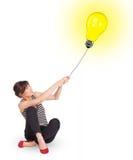 Happy woman holding a light bulb balloon. Happy young woman holding a light bulb balloon Royalty Free Stock Photography