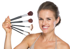 Happy young woman holding makeup brushes Stock Photos