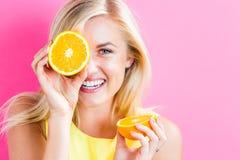 Happy young woman holding orange halves. Happy young woman holding oranges halves on a pink background royalty free stock photos