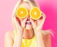 Happy young woman holding orange halves. Happy young woman holding oranges halves on a pink background stock image