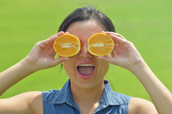 Happy young woman holding orange slices Stock Image