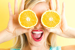 Happy Young Woman Holding Oranges Halves Stock Image