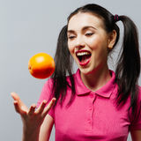 Happy young woman holding oranges halves on a pink background.  stock image