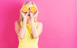 Happy young woman holding oranges halves. On a pink background Stock Image