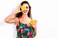 Happy young woman holding oranges halves Stock Photo