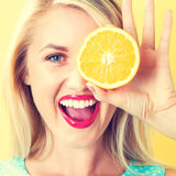 Happy young woman holding oranges halves. On a yellow background stock photos