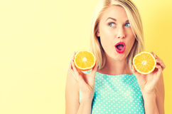 Happy young woman holding oranges halves Stock Images