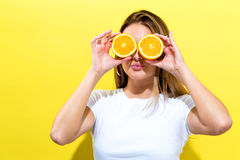 Happy young woman holding oranges halves Stock Photography