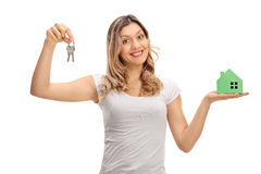 Happy young woman holding pair of keys and model house Stock Images