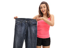 Happy young woman holding a pair of oversized jeans Royalty Free Stock Photos