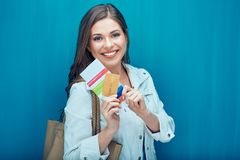 Happy young woman holding passport with ticket and credit card. Portrait of smiling girl on blue Royalty Free Stock Images
