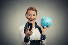 Happy young woman holding piggy bank looking at smart phone Stock Image
