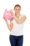 Happy young woman holding piggybank Royalty Free Stock Photo