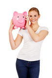 Happy young woman holding piggybank Royalty Free Stock Images