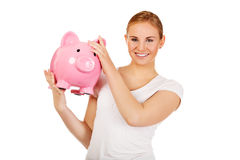 Happy young woman holding piggybank Royalty Free Stock Photos