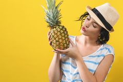 Happy young woman holding a pineapple royalty free stock images