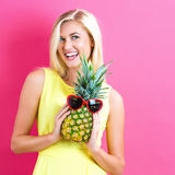 Happy young woman holding a pineapple. On a pink background Stock Photos